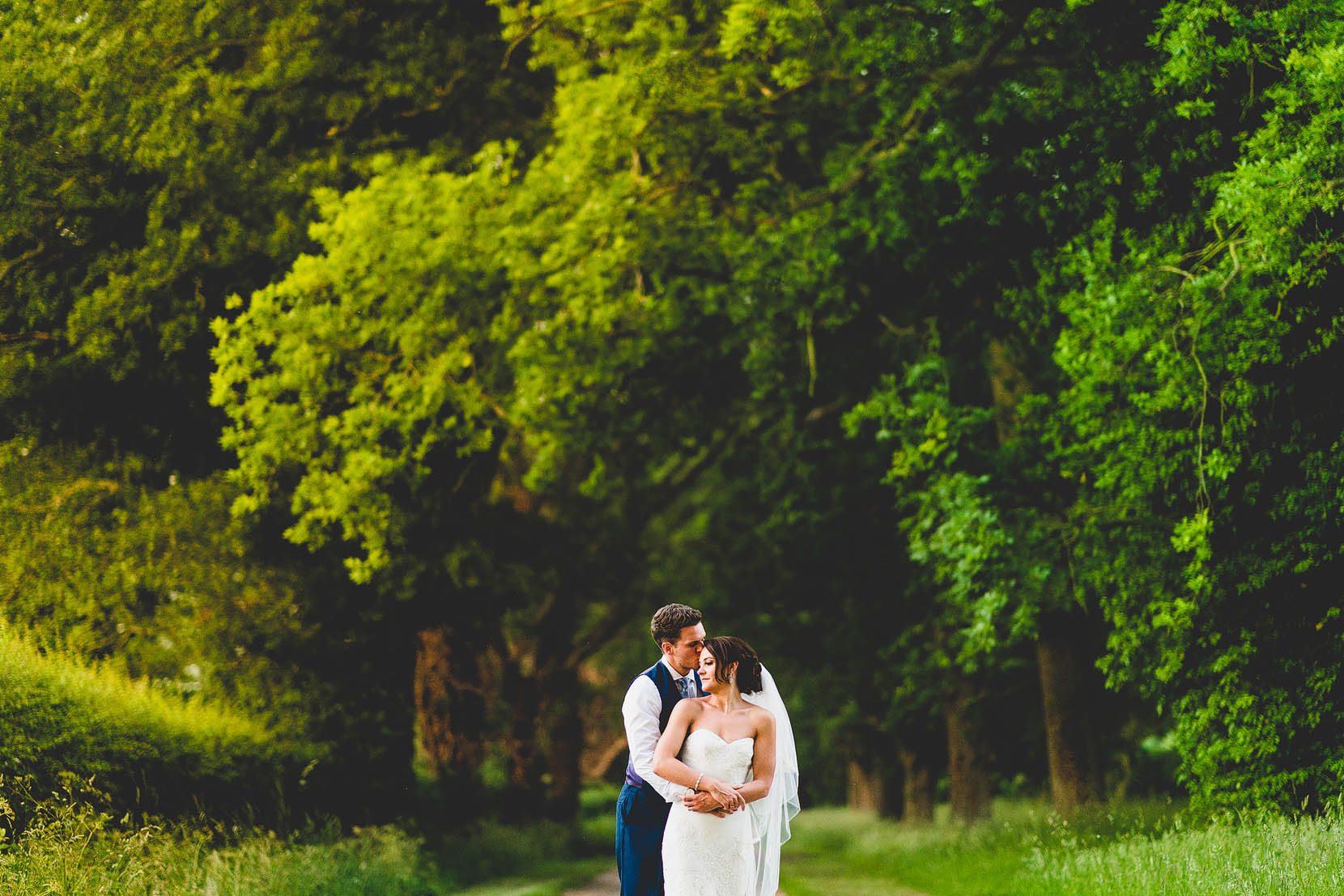 wedding photograph of daniel and melissa having a snuggle at woodhall manor in suffolk