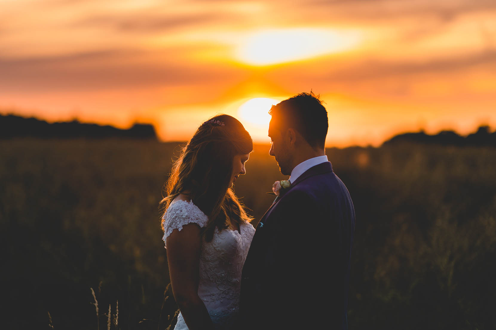 Michael & Philippa just married snuggle at sunset in ranwroth, norfolk