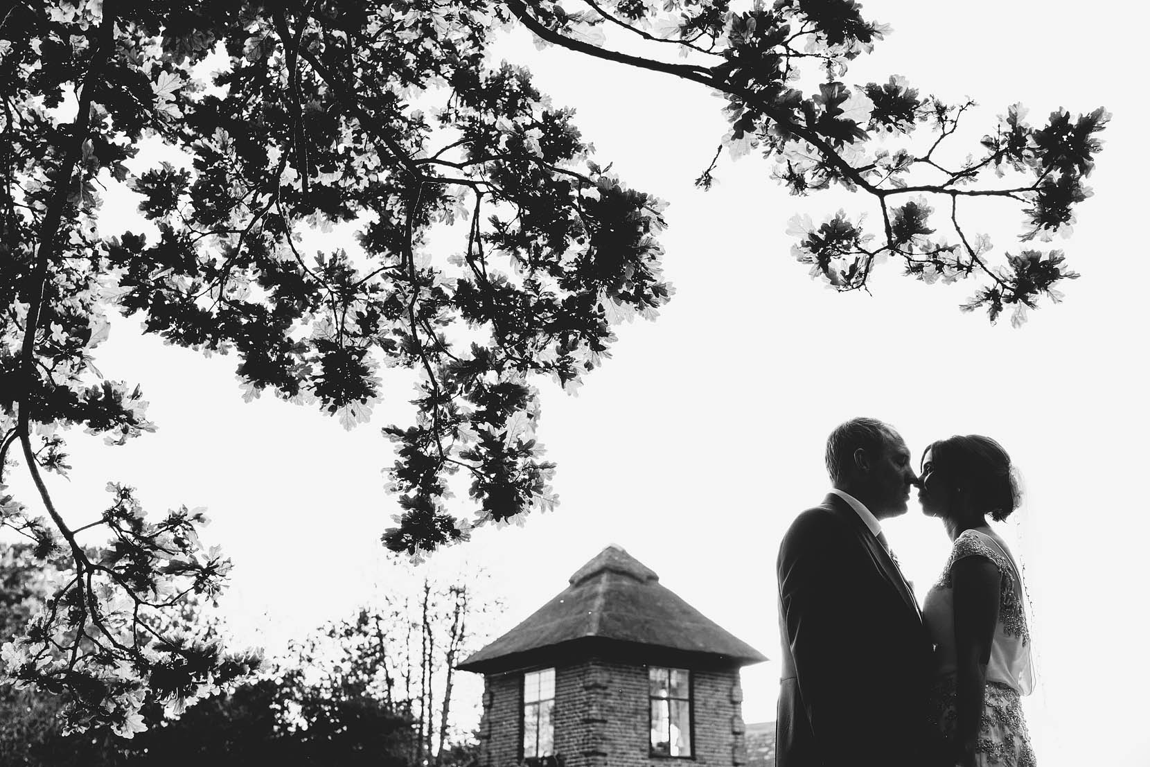 tom and kate have a kiss under the oak tree at southwood hall