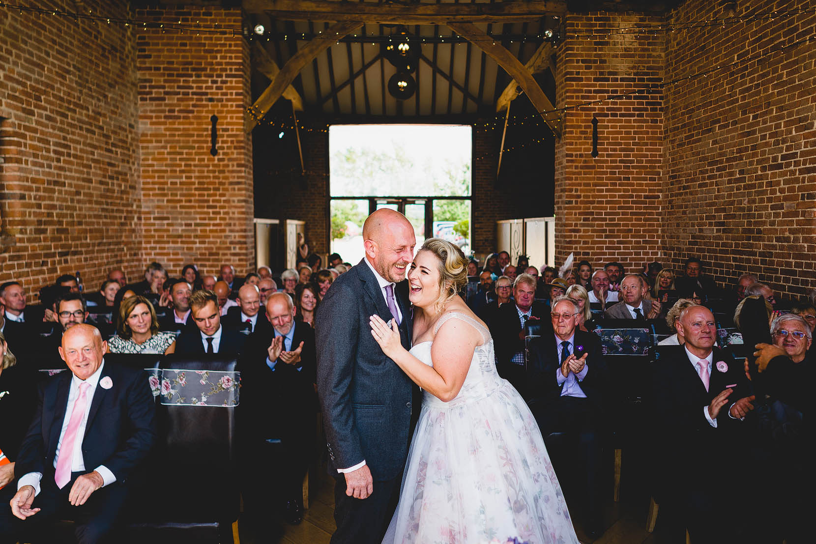 Paul and Elizabeth share a giggle at the top of the aisle in Coronation barn, Southwood hall Norfolk on their wedding day