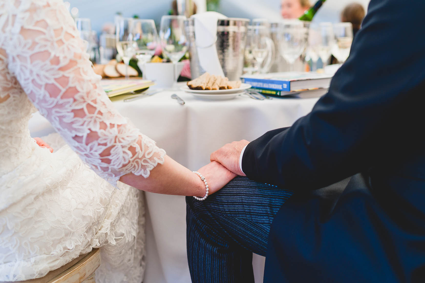 Hannah and Tim holding hands during the speeches at their wedding in Norfolk