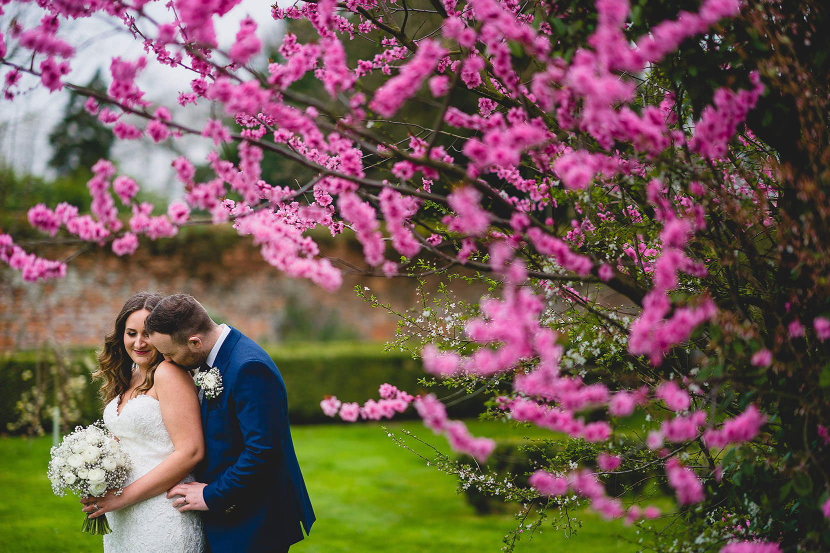 Laura and Grant having a snuggle in the blossum at Southwood Hall for their April Wedding