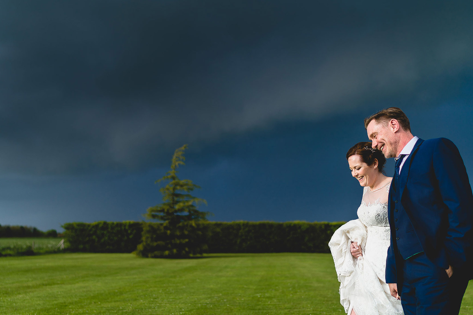 carl and paul walking out to get some bridal portaits on their wedding day at elms barn with a very stormy sky