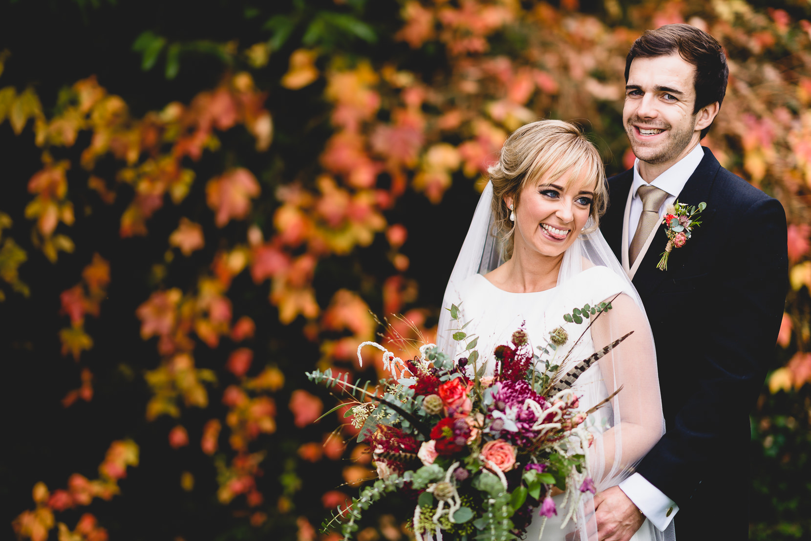 Autumn Wedding Photography in Norfolk with Catherine and Duncan cuddling in front of red leaves